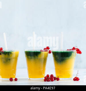 two colored fresh smoothies in glasses  orange banana juice